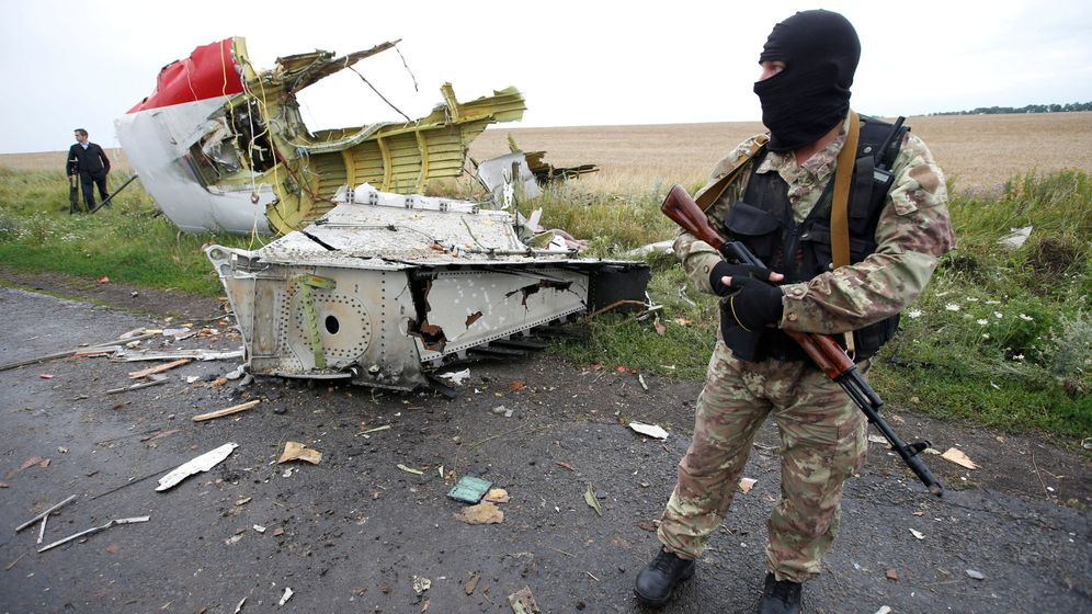 Foto: Un soldado prorruso separatista, ante un fragmento del avión estrellado MH17. (Reuters)