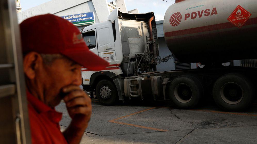 Foto: Un empleado de una gasolinera estatal, frente a un camión cisterna de PDVSA. (Reuters)