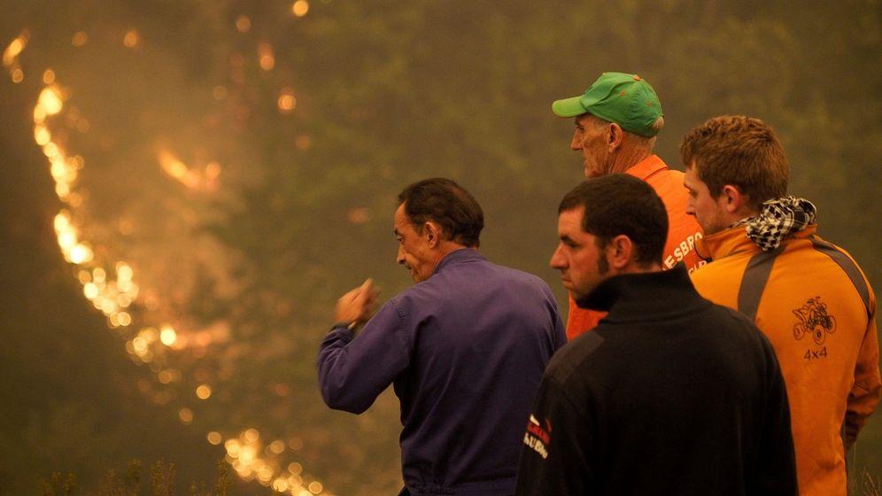 Foto: Varios vecinos, preocupados por las llamas junto al incendio forestal en las proximidades de la Reserva Natural de los Ancares (Lugo). (EFE)