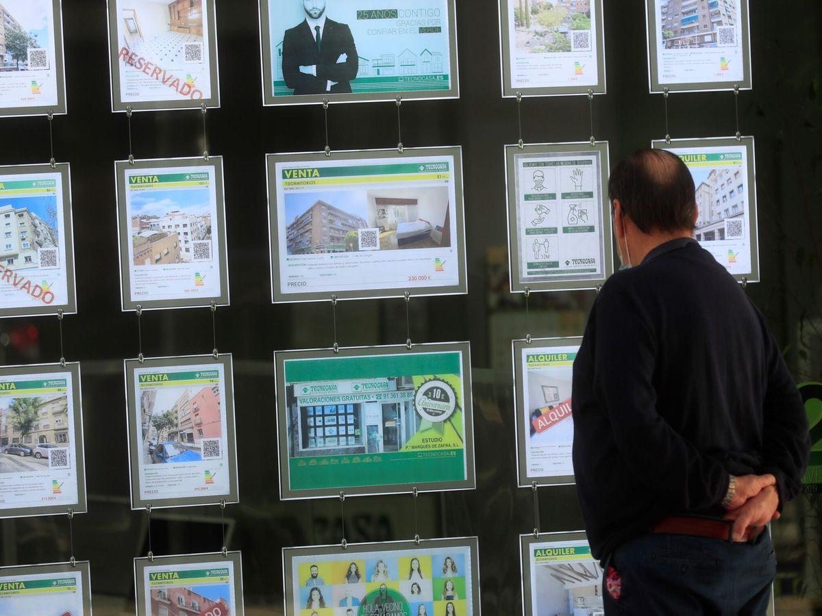 Foto: Un hombre mira unos carteles en una inmobiliaria de Madrid. (EFE)