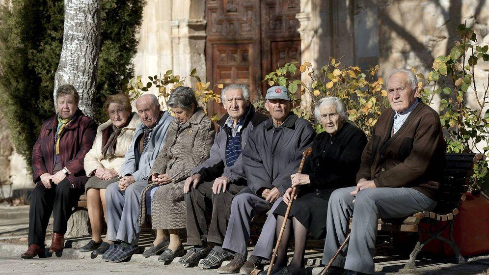Foto: Varios ancianos toman el sol en unos bancos de Olmeda de la Cuesta, Cuenca, en una foto de archivo. (EFE)