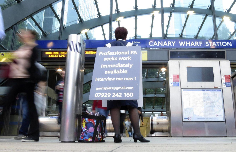 Foto: Gerri Spiers, una británica en paro, pide empleo en la estación de metro de Canary Wharf, en el distrito financiero de Londres. (Reuters)