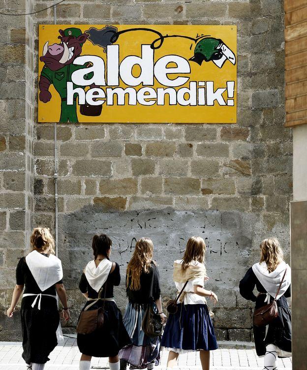 Foto: Un grupo de jóvenes pasan junto a un cartel alusivo a la Guardía Civil en Alsasua para celebrar el 'Ospa Eguna' o Día de la Huida. (EFE)