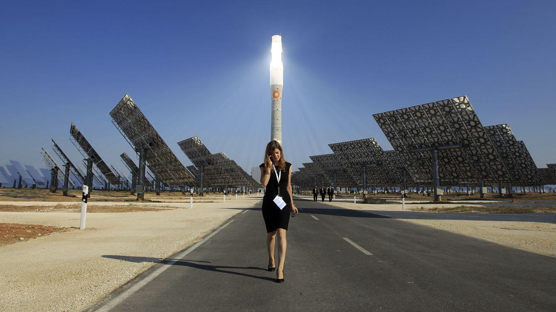 Foto: Una mujer camina entre los paneles de la planta de energía Gemasolar el día de su inauguración. (Reuters)