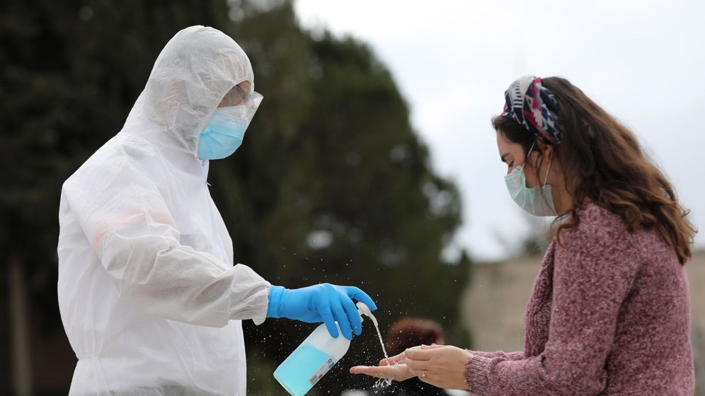 Foto: Un trabajador sanitario dispensa gel desinfectante a una mujer en Jerusalén, Israel (EFE)