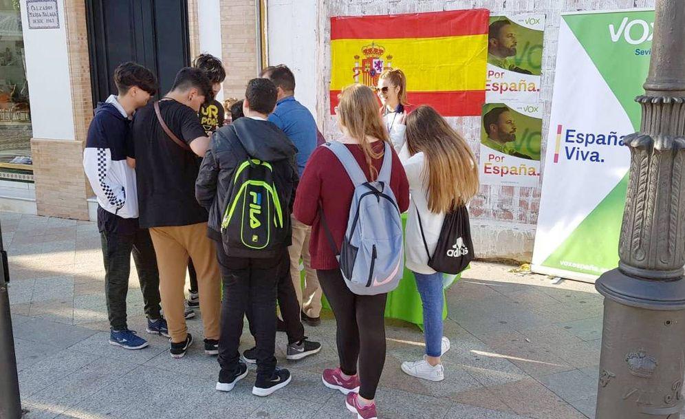 Foto: Grupo de jóvenes en Los Palacios frente a un cartel de Vox.