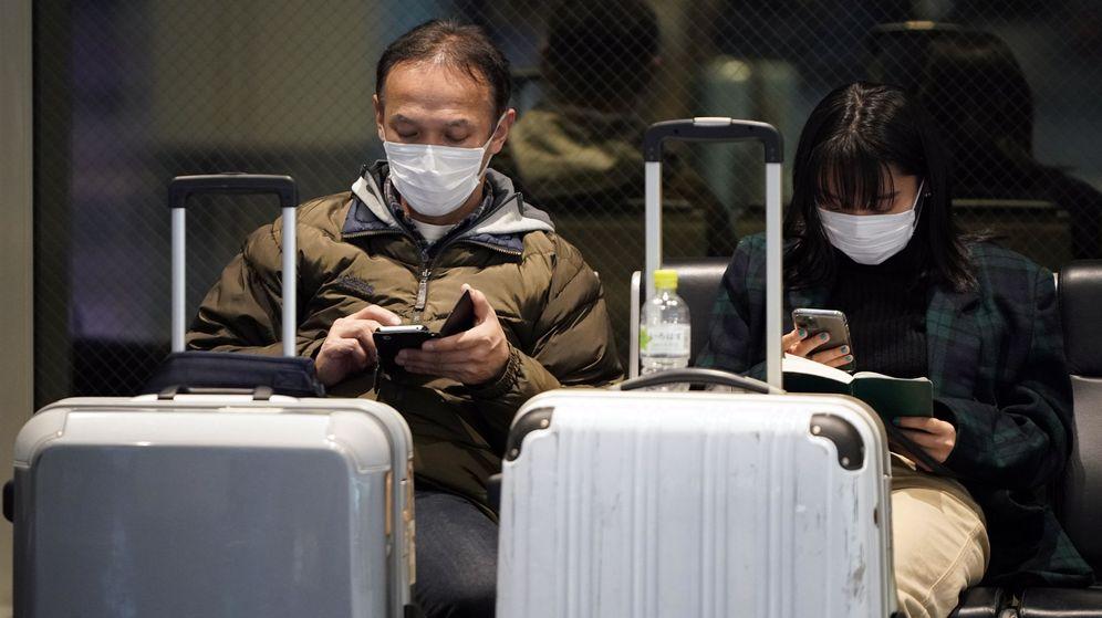 Foto: Dos viajeros, protegidos frente al virus de Wuhan. (Reuters)