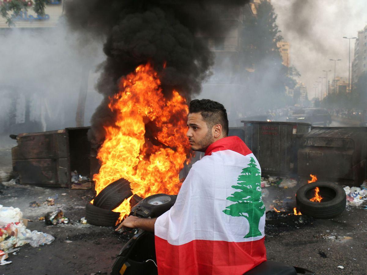 Foto: Soldados del Ejército libanés se protegen de las piedras durante los enfrentamientos con los partidarios de Hariri. (EFE)