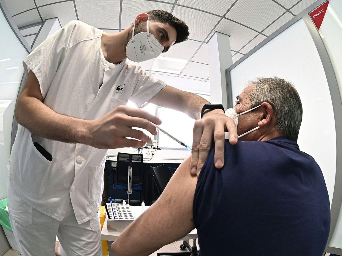 Foto: Un sanitario vacuna contra el coronavirus a un hombre en el hospital de Alcalá de Henares. (EFE)