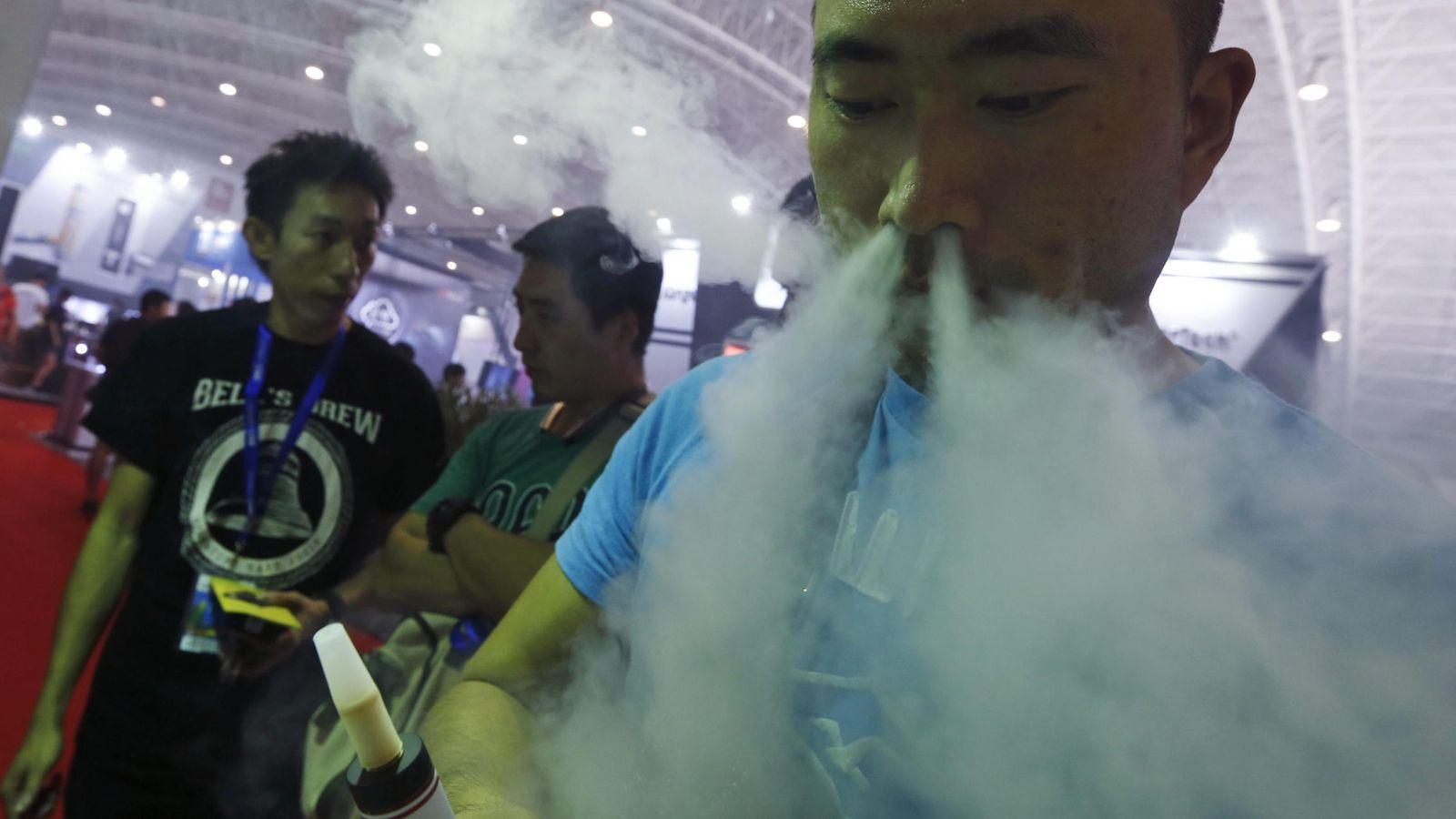 """Foto: Un visitante prueba un cigarrillo electrónico en un stand de la feria """"Vape China Expo"""" del cigarrillo electrónico"""