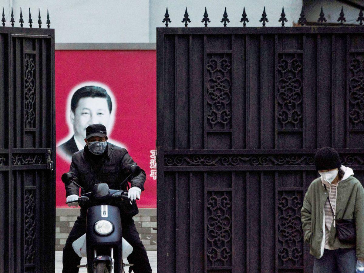 Foto: Dos personas con mascarillas, delante de un retrato del presidente Xi Jinping. (Reuters)