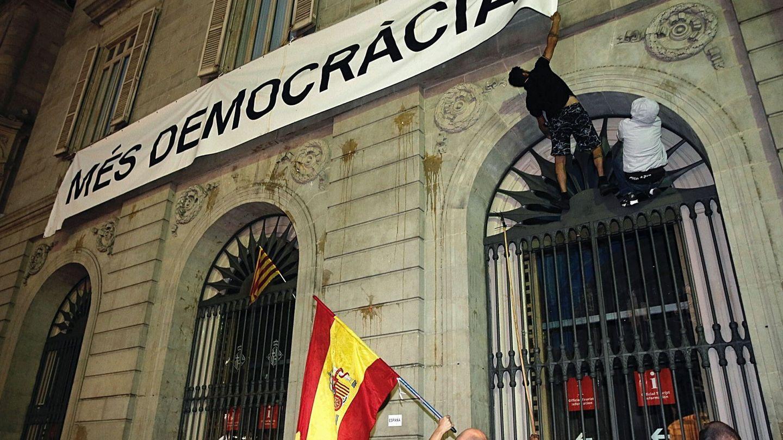 Dos personas intentan arrancar la pancarta colgada en el ayuntamiento de Barcelona. (EFE)