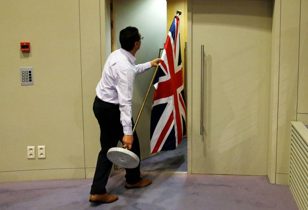 Foto: Un trabajador coloca una bandera británica antes de una rueda de prensa de David Davis y Michel Barnier en Bruselas. (Reuters)