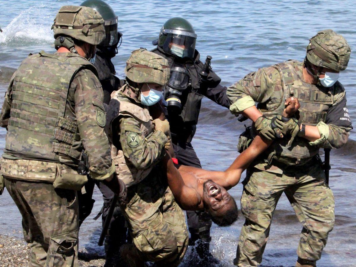 Foto: Miembros del Ejército de Tierra trasladan a un migrante que había logrado cruzar uno de los espigones fronterizos de Ceuta durante la crisis del pasado mayo. (EFE)
