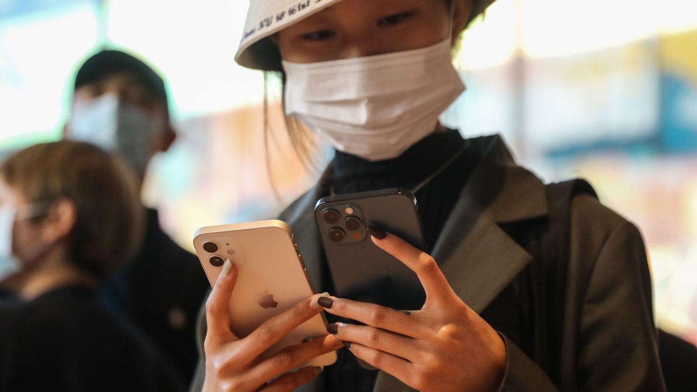 Una mujer sostiene un iPhone 12 y un iPhone 12 Pro en una tienda de Apple en Pekín. (Reuters)