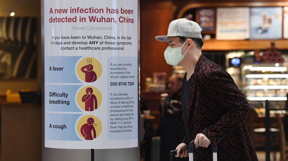Foto: Un hombre con mascarilla arastra sus maletas por el aeropuerto de Londres-Heathrow. (EFE)