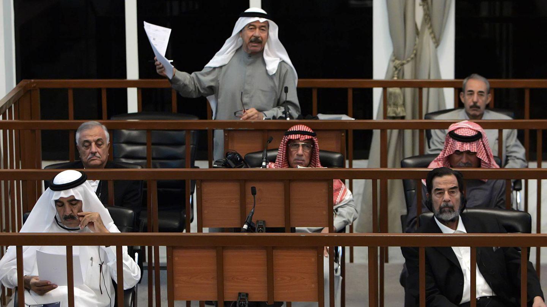 Alí Hassan Al Mayid, 'Alí el Químico', habla durante su juicio en octubre de 2006. Abajo a la derecha, su primo, Saddam Hussein. (Reuters)