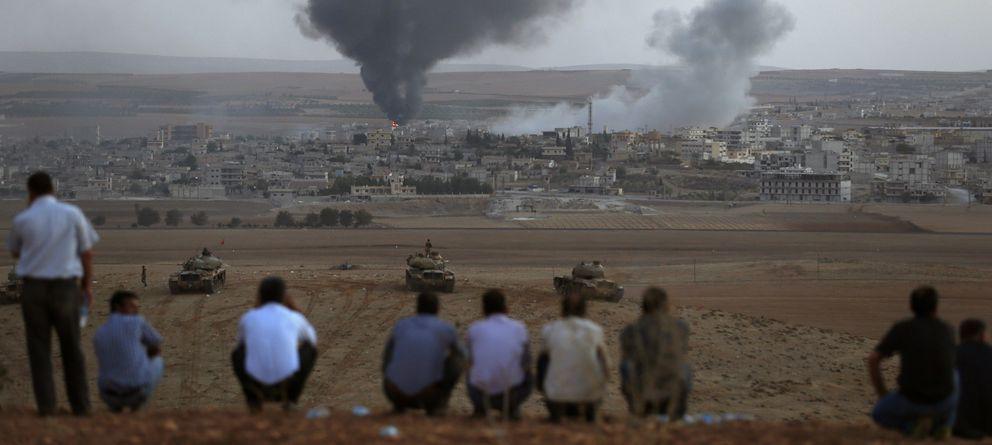 Foto: Kurdos observan desde territorio turco el humo provocado por los combates en Kobani durante la ofensiva del Estado Islámico (Reuters).