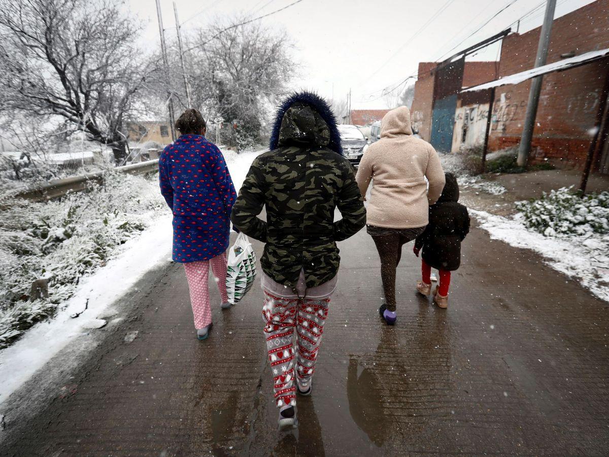Foto: Varios residentes de la Cañada Real caminan bajo la nieve este jueves. (EFE)