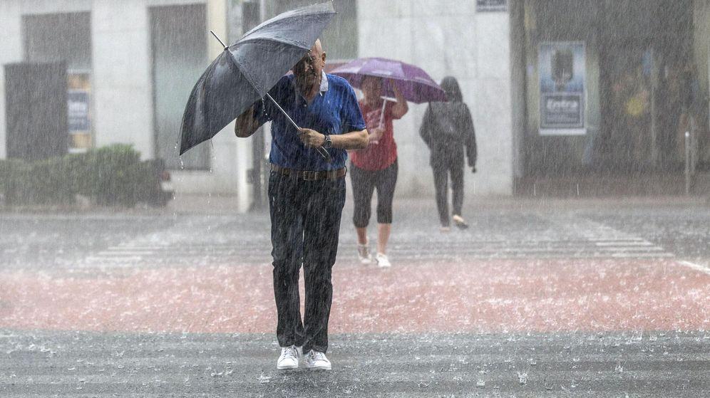 Foto: Varias personas cruzan una calle tratando de protegerse con un paraguas de una fuerte tormenta en Valencia. (EFE)