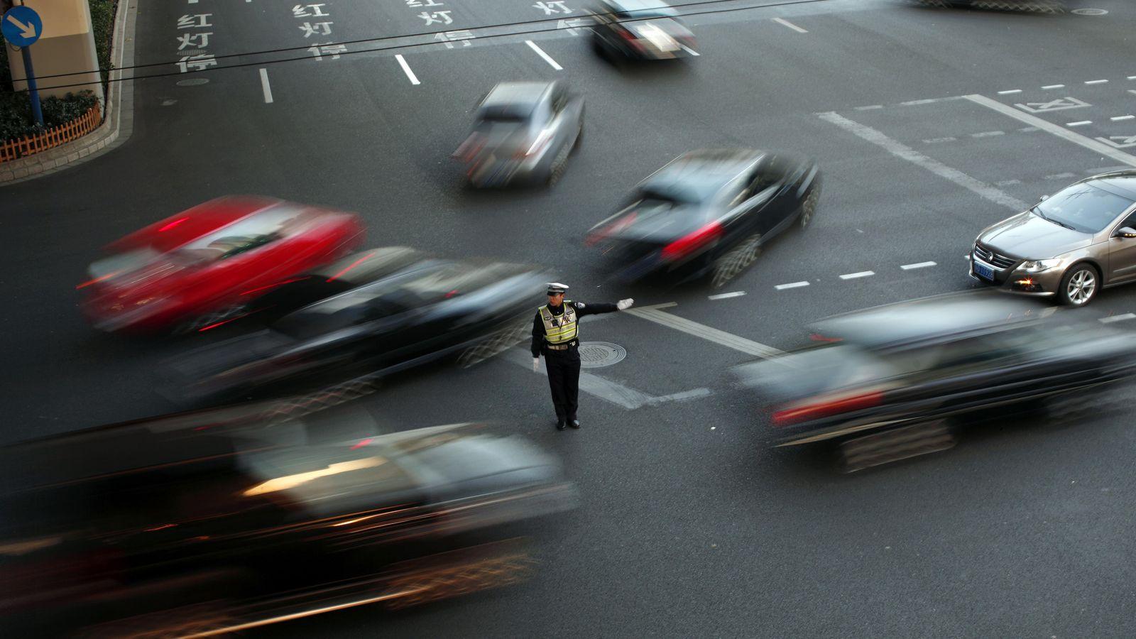 Foto: Un policía regula el tráfico en una ciudad del centro de Shangái. (Reuters/Carlos Barria)