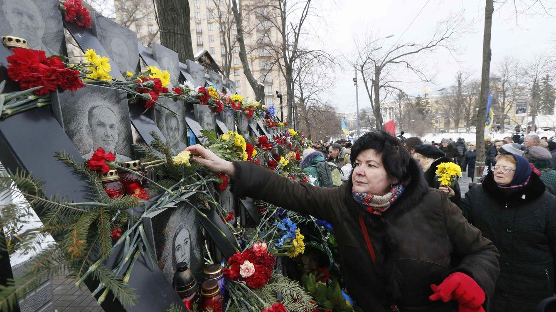 Foto: Una mujer deposita flores en un monumento dedicado a las personas que murieron durante la revuelta del Maidan en 2014, en Kiev, el 20 de febrero de 2014. (Reuters)