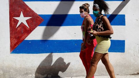Dos mujeres caminan frente a un graffiti de la bandera de Cuba