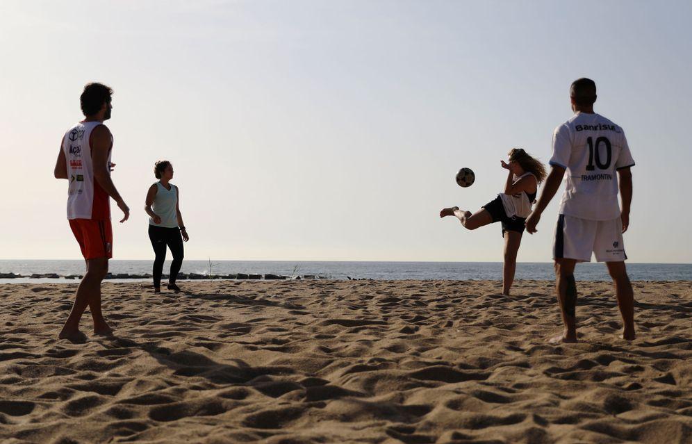 Foto: Cuatro personas juegan con el balón en la playa de la Barceloneta, en la capital catalana, este 8 de mayo. (Reuters)