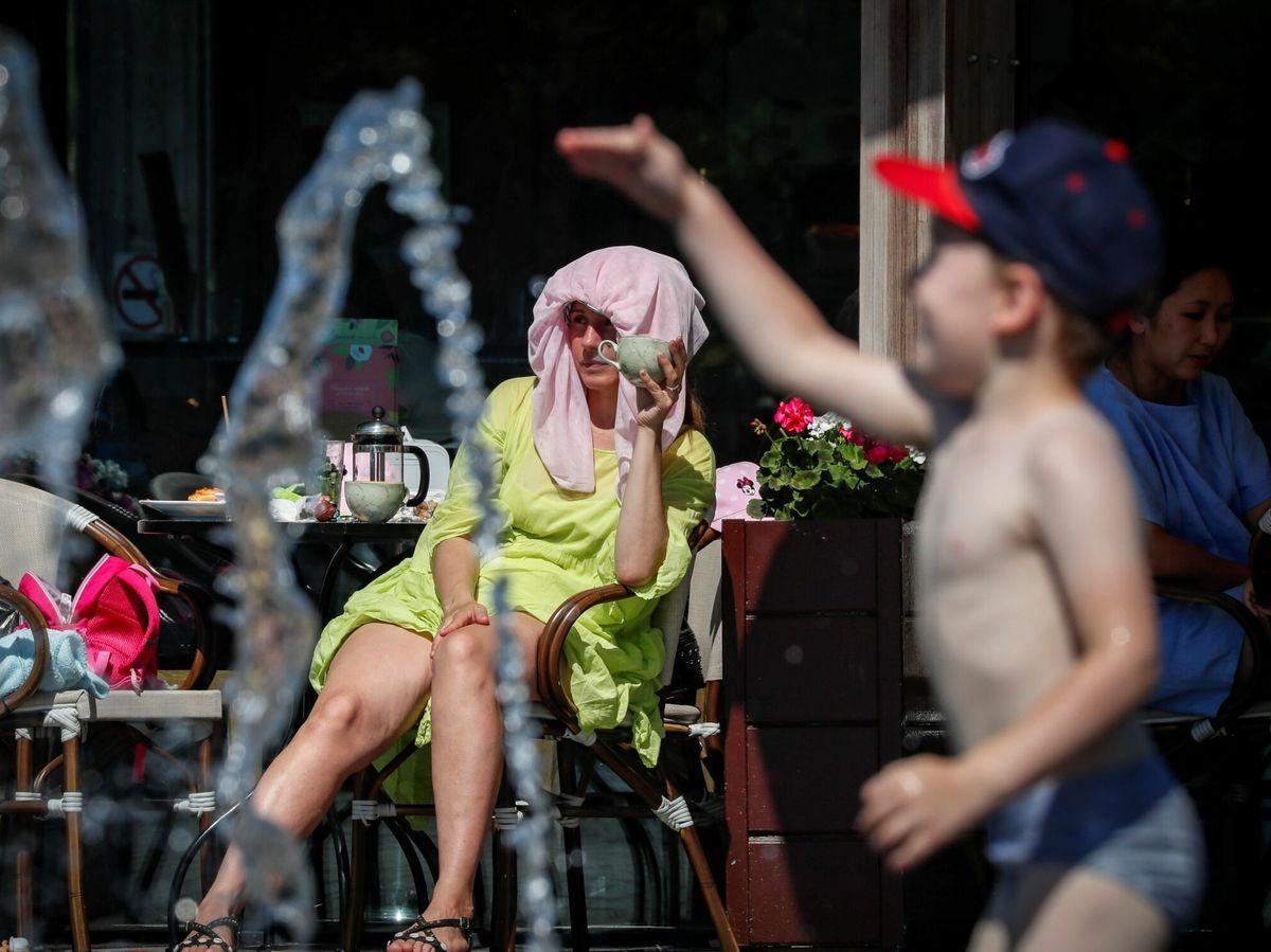 Foto: Un niño juega en una fuente mientras su madre se protege del calor (EFE)