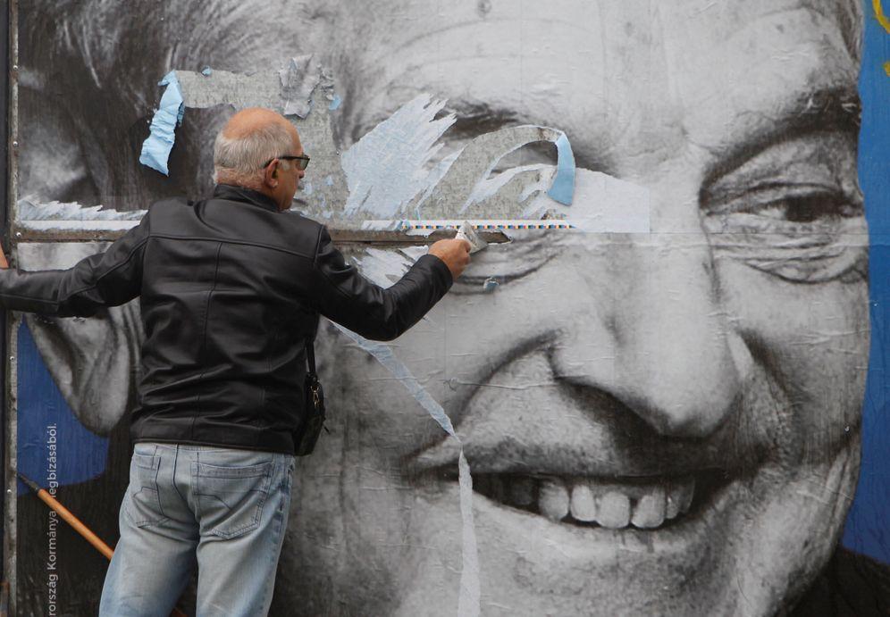 Foto: Activistas húngaros tratan de quitar un cartel gubernamental sobre George Soros. (Bernadett Szabo/Reuters)