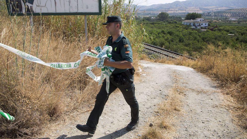 Foto: Un Guardia Civil retira la cinta de la zona acotada en la vía férrea donde esta mañana un maquinista encontró el cuerpo de la pequeña. (EFE)