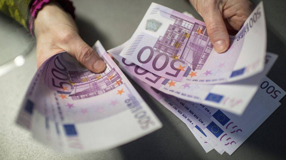 Foto: Un hombre sostiene varios billetes de 500 euros en su mano. (EFE)