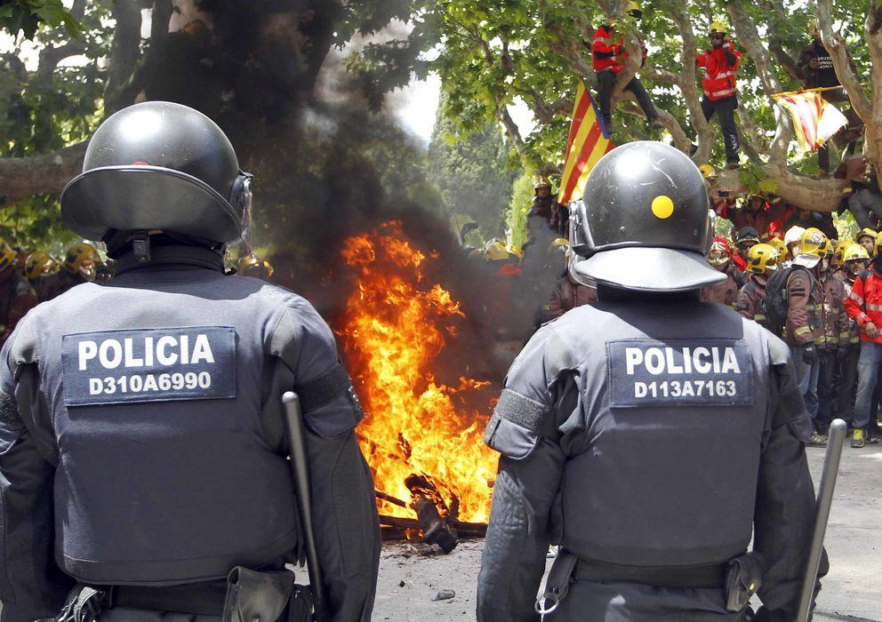 Foto: Dos 'mossos' observan una hoguera provocada por los bomberos que protestan ante el Parlament de Catalunya. (EFE)