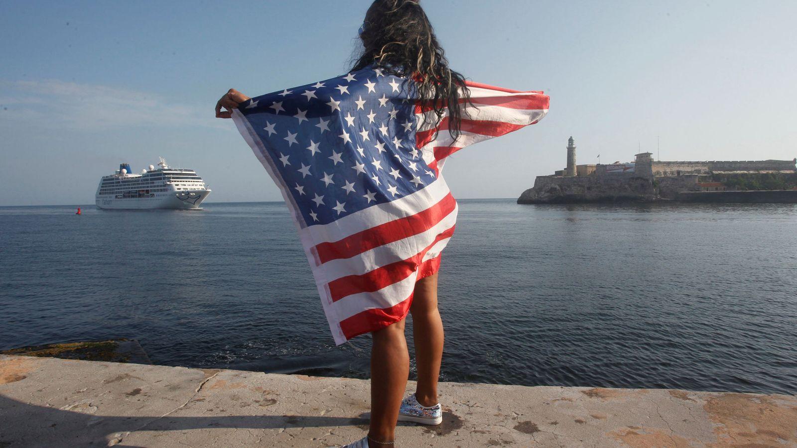 Foto: Una mujer con una bandera estadounidense aguarda la llegada del crucero 'Adonia' al puerto de La Habana, el 2 de mayo de 2016. (Reuters)