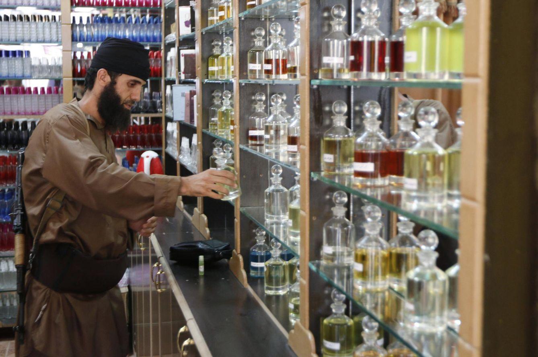 Foto: Un miliciano del autodenominado Estado Islámico inspecciona perfumes en Raqqa, su 'capital' en Siria. (Reuters)
