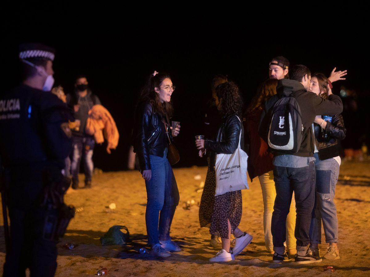 Foto: Jóvenes desalojados de la Barceloneta tras el fin del estado de alarma. (EFE)