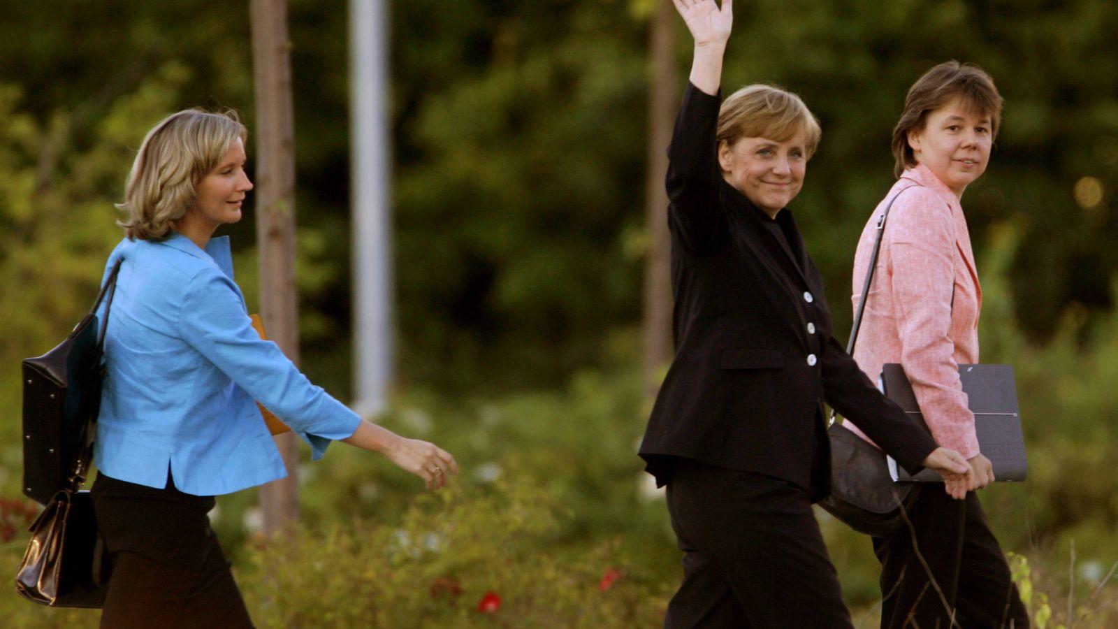 Foto: Angela Merkel junto a su asesora Beate Baumann (derecha) y su portavoz Eva Christiansen (izquierda), en 2005. (Reuters)