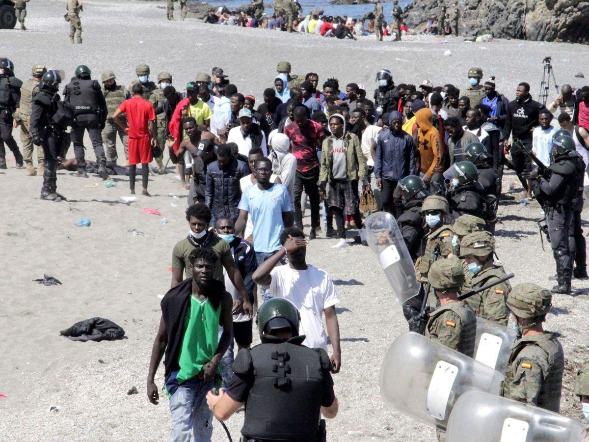 Foto: Soldados vigilan a un grupo de inmigrantes en Ceuta. (EFE)