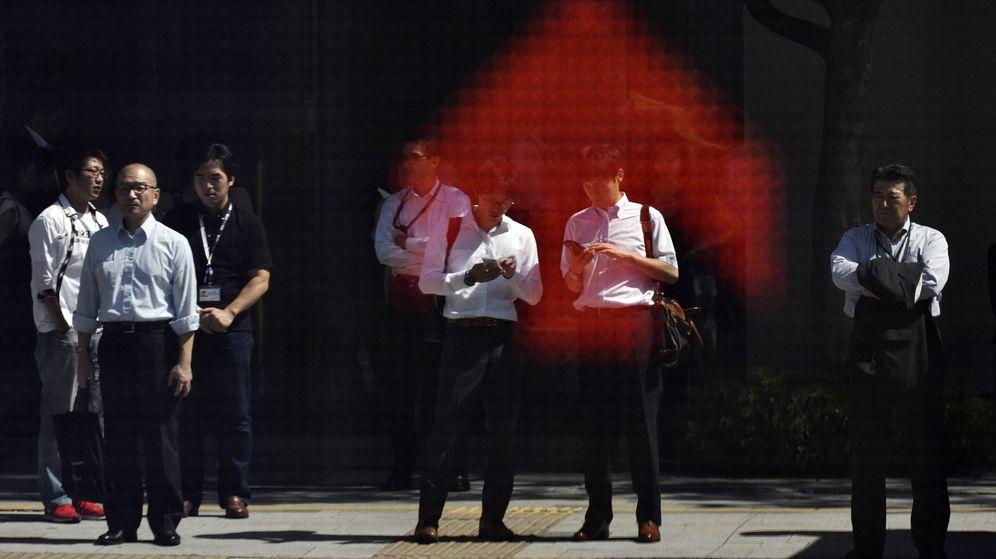 Foto: Peatones se reflejan en un cuadro indicador del mercado bursátil en Tokio (Japón). (EFE)