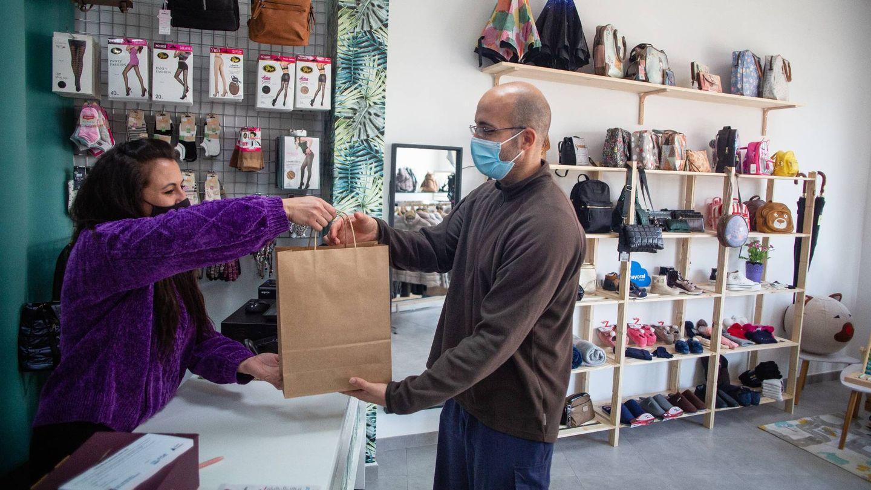Cristina Carnero, propietaria de Mis Zapatos y Complementos, entregando un paquete al repartidor de Mojizon. (Fernando Ruso)