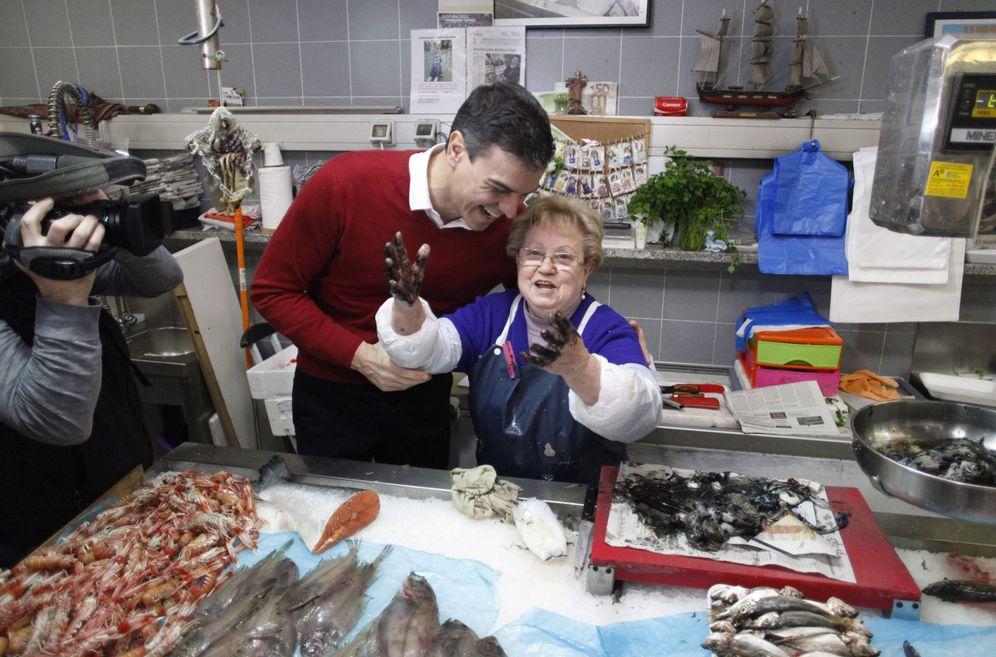Foto: Pedro Sánchez conversa con una comerciante del mercado de la plaza de Lugo, en A Coruña, este 10 de marzo. (EFE)