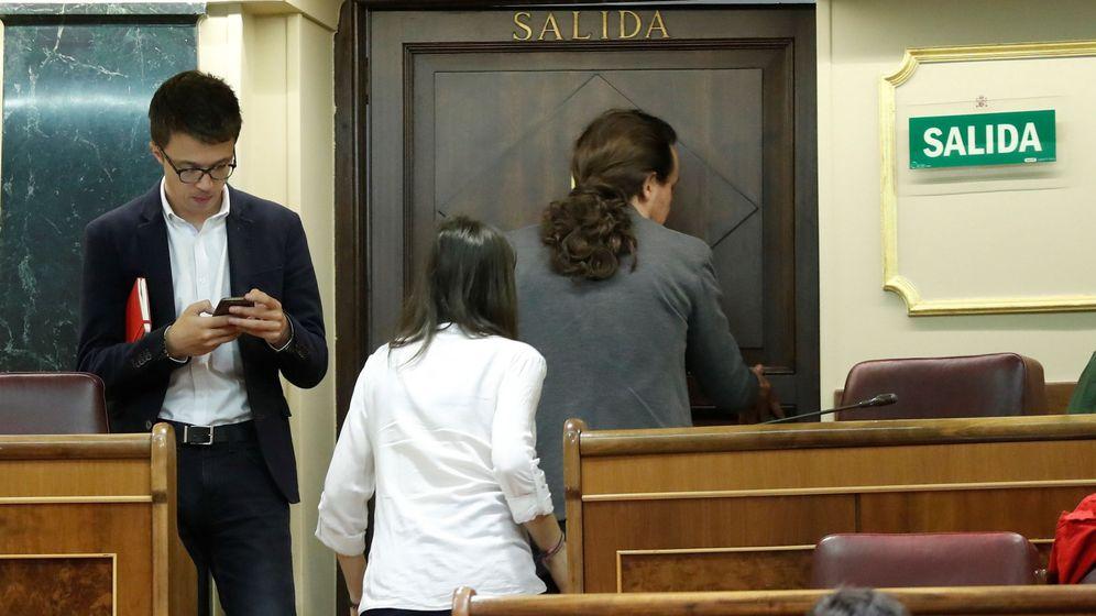 Foto: Íñigo Errejón consulta su móvil mientras Irene Montero y Pablo Iglesias abandonan el Congreso. (EFE)