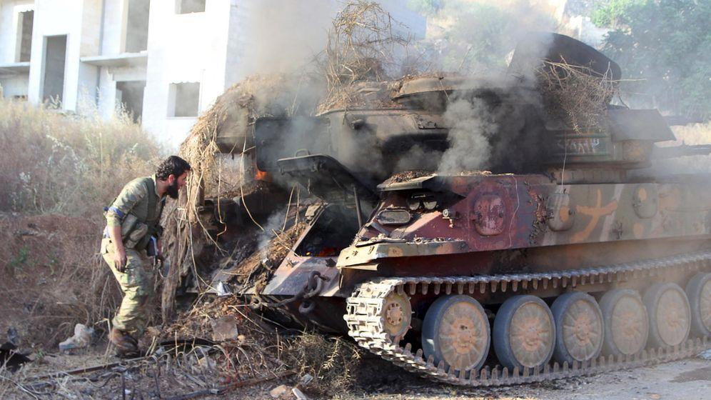 Foto: Un miembro del Frente Al Nusra inspecciona un vehículo antiaéreo en llamas tras la batalla de Ariha, en la provincia de Idlib (Reuters)