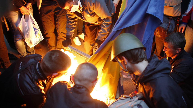 Manifestantes prorrusos queman una bandera de Ucrania en Donéstsk. (Reuters)