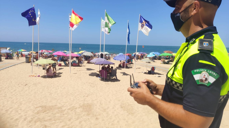 Foto: Josemari Gálvez, policía local de Chipiona, pilotando uno de los drones que vigila aforo de las playas del municipio gaditano.