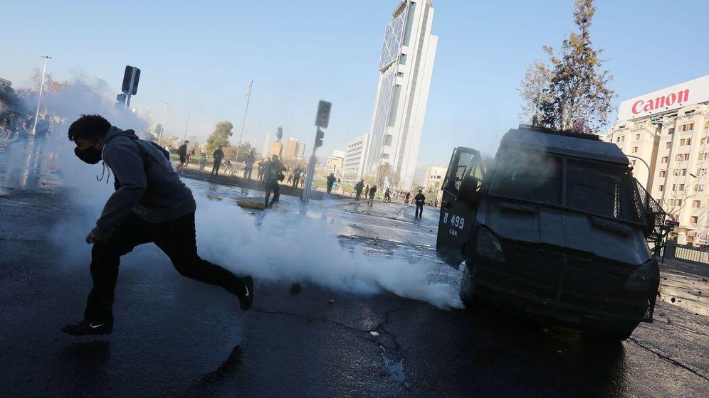 Foto: Un hombre corre del gas y un vehículo de la policía. (EFE)