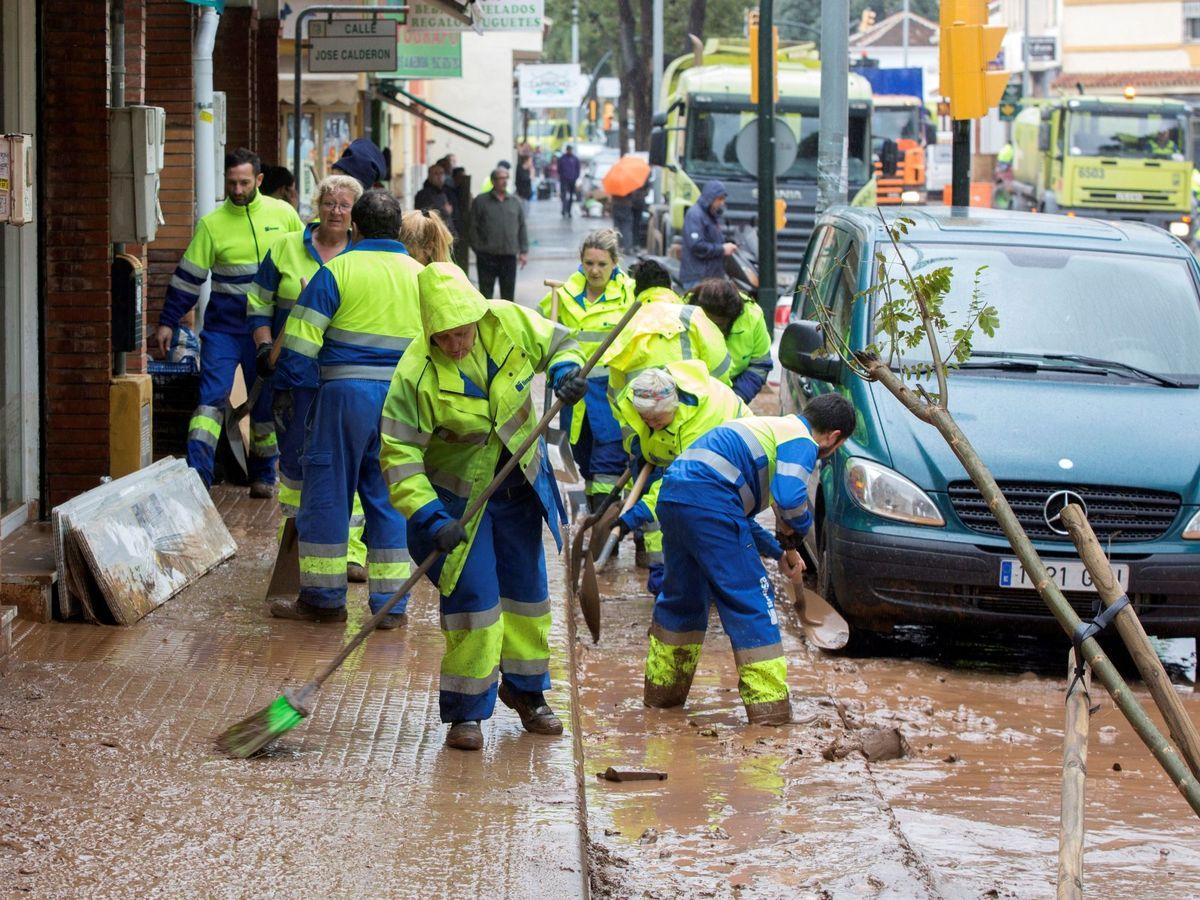 Foto: Operarios de limpieza de Málaga trabajando en la tromba de agua (EFE).