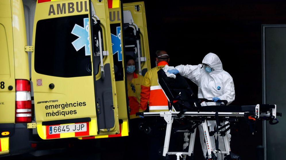 Foto: Un técnico sanitario desinfecta la camilla de una ambulancia en la entrada de urgencias del Hospital de Bellvitge. (EFE)