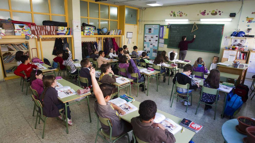Foto: Una profesora escribe en la pizarra de un colegio público madrileño. (Reuters/Sergio Pérez)