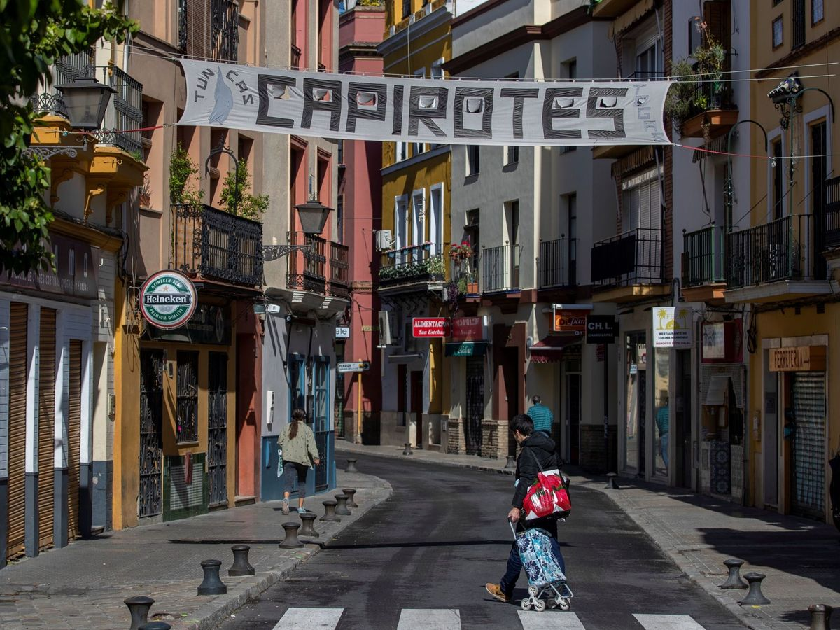 Foto: Un hombre camina bajo el cartel de un comercio de Sevilla que anuncia capirotes para la Semana Santa (EFE)